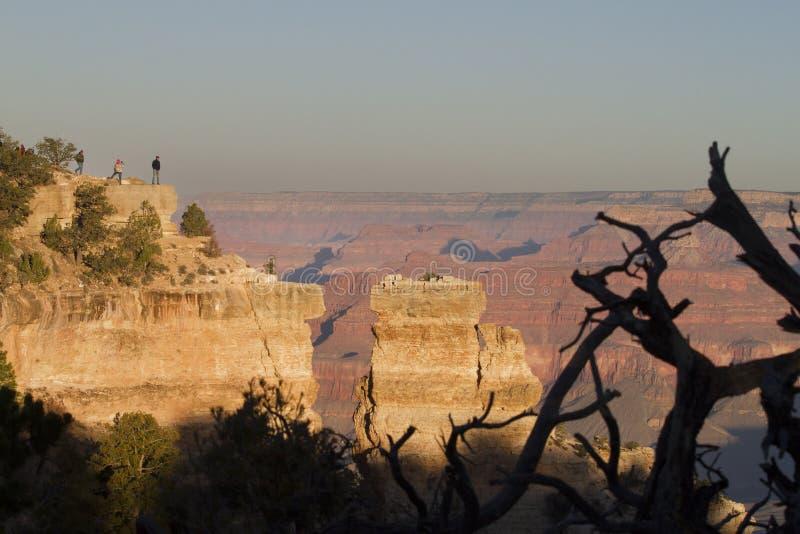 Μεγάλοι τουρίστες φαραγγιών που προσέχουν την ανατολή σε έναν απότομο βράχο στοκ φωτογραφίες