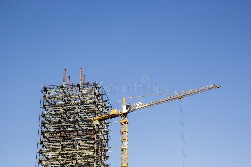 Μεγάλος κίτρινος γερανός κατασκευής και ο σκελετός ενός ατελούς στοκ φωτογραφία