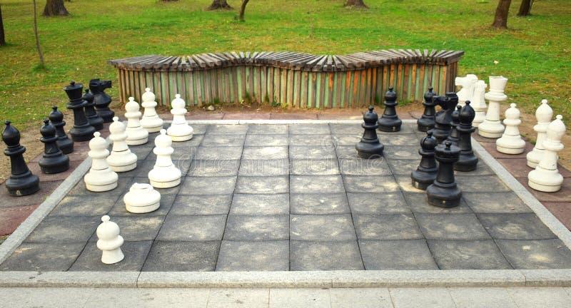 Μεγάλος πίνακας σκακιού με τα τεράστια κομμάτια στο πάρκο στοκ εικόνα