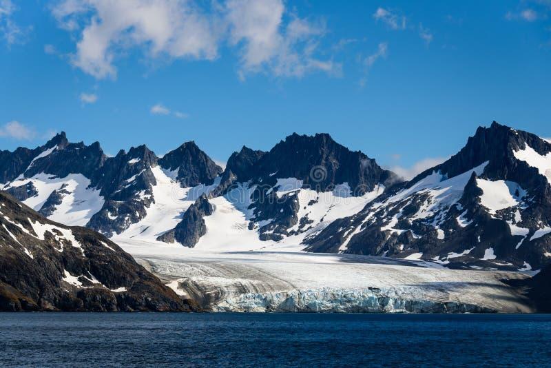 Μεγάλος παγετώνας που περιβάλλεται από τα χιονώδη βουνά που τροφοδοτο στοκ φωτογραφία