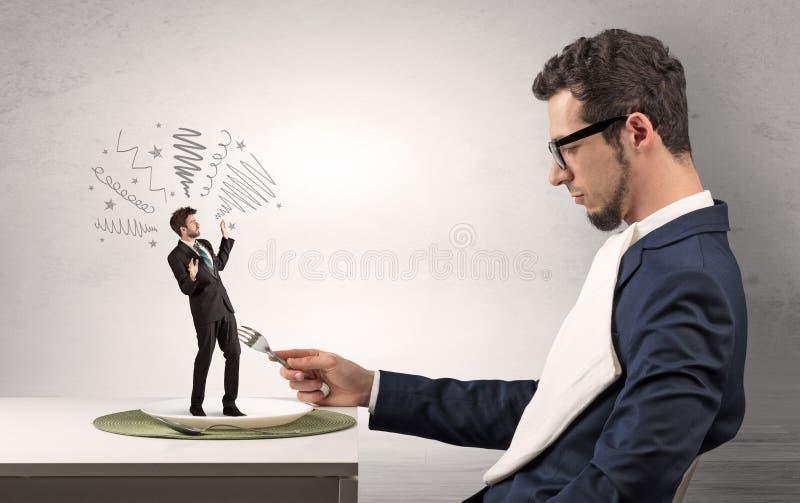 Μεγάλος προϊστάμενος που τρώει το μικρό επιχειρηματία στοκ φωτογραφία