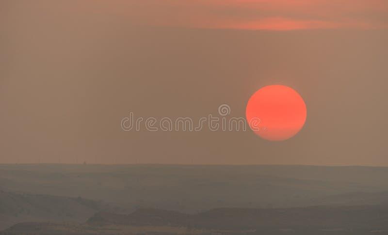 Μεγάλος στρογγυλός καυτός πορτοκαλής ήλιος που πλησιάζει στο θερινό ηλιοβασίλεμα οριζόντων στοκ φωτογραφία