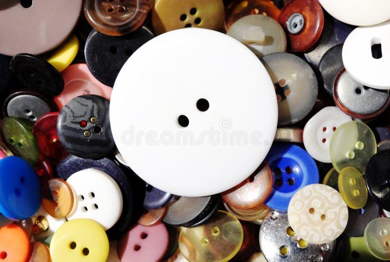 Μεγάλο άσπρο κουμπί που βάζει σε άλλα μικρότερα ζωηρόχρωμα κουμπιά στοκ φωτογραφία με δικαίωμα ελεύθερης χρήσης