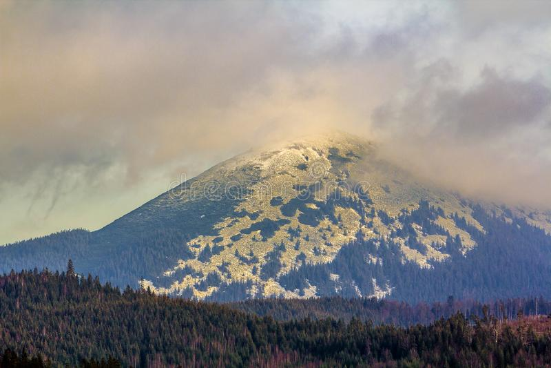 Μεγάλο βουνό με τα ομιχλώδη σύννεφα πέρα από την κορυφή στοκ φωτογραφία