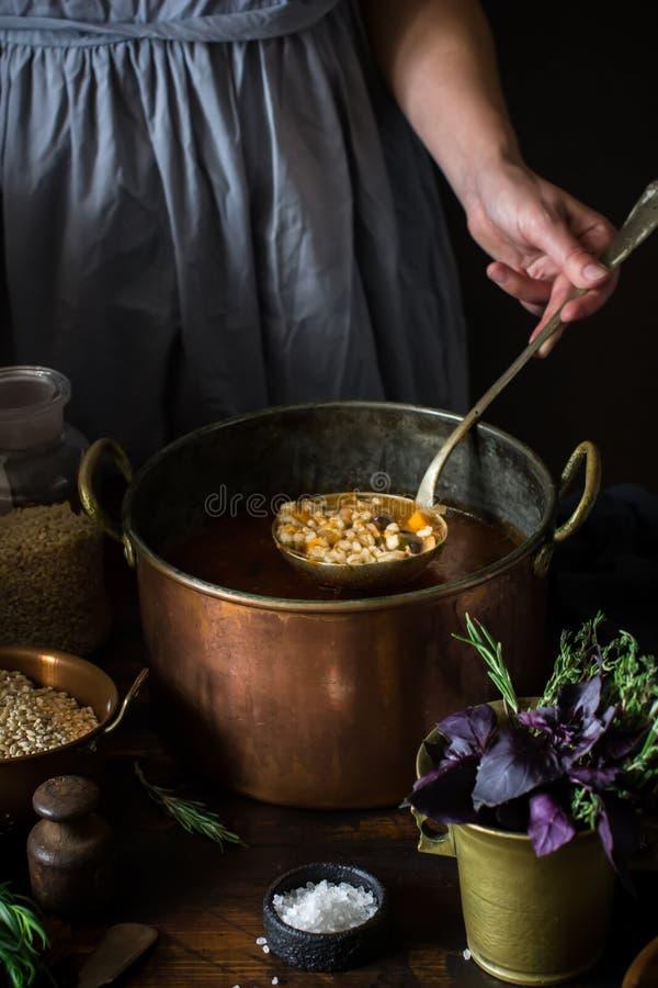 Μεγάλο εκλεκτής ποιότητας τηγάνι χαλκού με τη σούπα και κουτάλα στο θηλυκό χέρι στοκ φωτογραφία