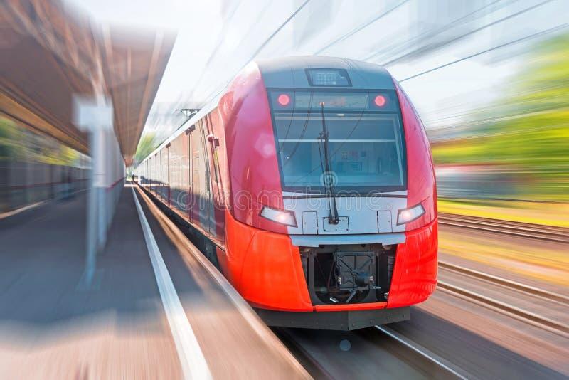Μεγάλο ηλεκτρικό τραίνο με τη θαμπάδα κινήσεων τραίνο σιδηροδρομικών σταθμών στοκ εικόνες