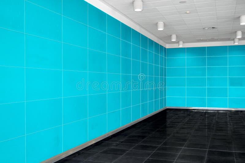 Μεγάλο κενό εσωτερικό δωματίων με το φωτεινό μπλε τοίχο, whire ανώτατο όριο και στοκ εικόνα με δικαίωμα ελεύθερης χρήσης