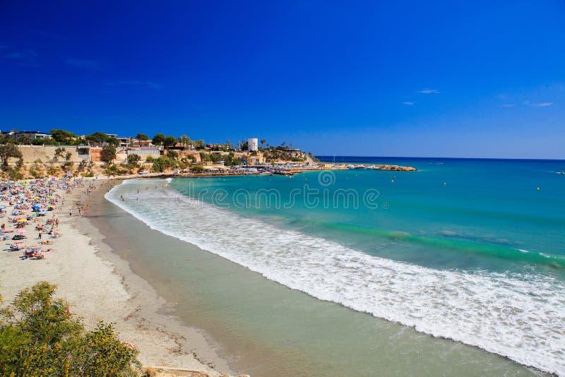 Μεγάλο κύμα, τυρκουάζ θάλασσα και αμμώδης παραλία στην Ισπανία στο Κόστα Μπλάνκα στοκ εικόνα