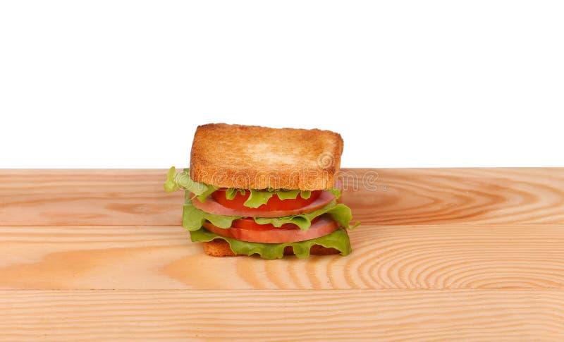 Μεγάλο σάντουιτς με τα φρέσκα λαχανικά στον ξύλινο πίνακα στο άσπρο υπόβαθρο στοκ φωτογραφίες
