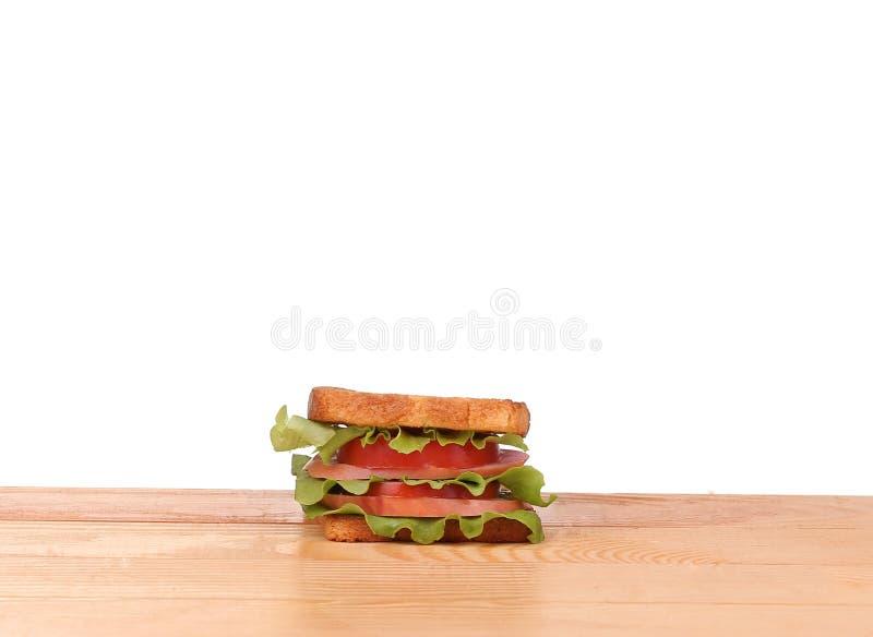 Μεγάλο σάντουιτς με τα φρέσκα λαχανικά στον ξύλινο πίνακα στο άσπρο υπόβαθρο στοκ εικόνες με δικαίωμα ελεύθερης χρήσης