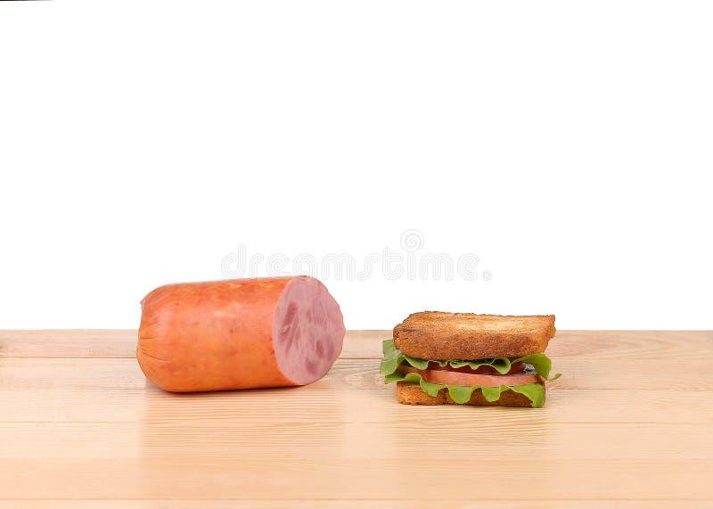 Μεγάλο σάντουιτς με τα φρέσκα λαχανικά στον ξύλινο πίνακα στο άσπρο υπόβαθρο στοκ εικόνες