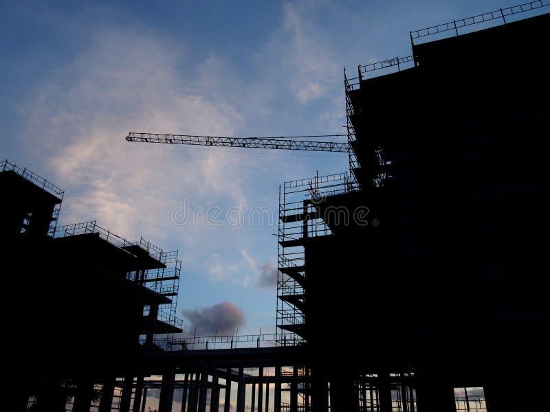 Μεγάλο σύγχρονο εργοτάξιο οικοδομής στη σκιαγραφία με τα υλικά σκαλωσιάς και κιγκλιδώματα που καλύπτουν τη δομή με το γερανό στο  στοκ φωτογραφίες