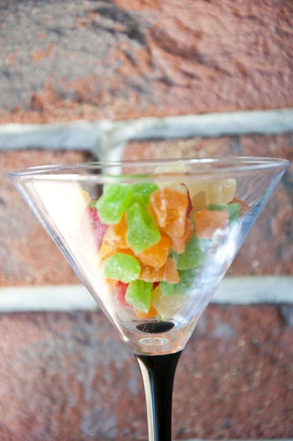 Μεγάλο martini γυαλί που γεμίζουν με τις gummy καραμέλες στο υπόβαθρο τουβλό στοκ εικόνα με δικαίωμα ελεύθερης χρήσης
