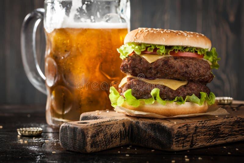 Μεγάλες χάμπουργκερ και κούπα της μπύρας στοκ φωτογραφίες με δικαίωμα ελεύθερης χρήσης