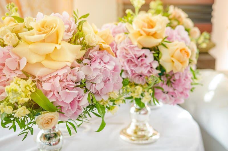 Μεγάλη ανθοδέσμη των ρόδινων hydrangeas και των κίτρινων στάσεων τριαντάφυλλων στον πίνακα γευμάτων στοκ φωτογραφία