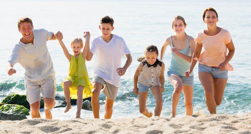 Μεγάλη θετική οικογένεια έξι ανθρώπων που τρέχουν από κοινού στοκ φωτογραφία με δικαίωμα ελεύθερης χρήσης