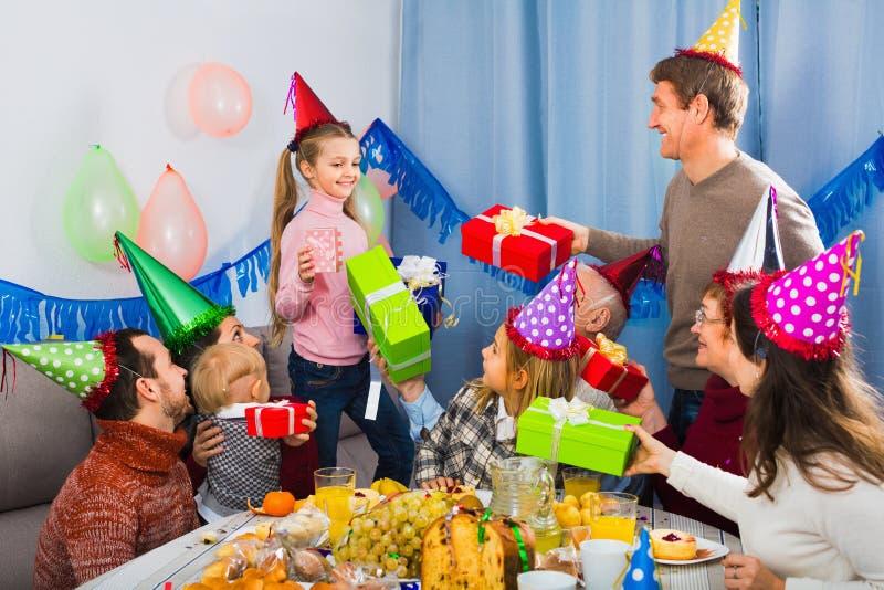 Μεγάλη οικογένεια που παρουσιάζει τα δώρα στο κορίτσι κατά τη διάρκεια της γιορτής γενεθλίων στοκ εικόνες