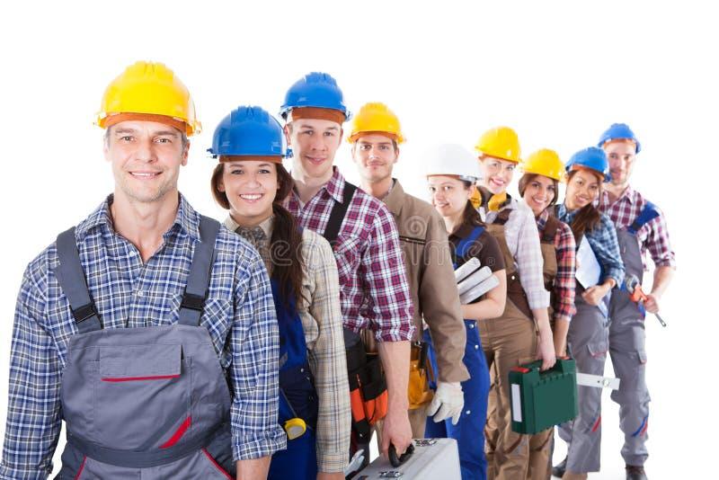Μεγάλη ομάδα εργατών οικοδομών που περιμένουν στη σειρά επάνω στοκ εικόνες