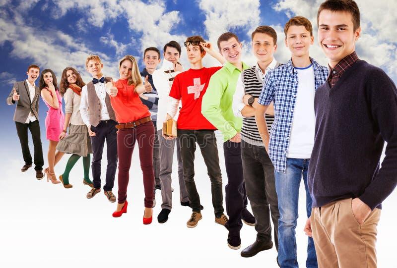 Μεγάλη ομάδα ευτυχών πολύχρωμων ντυμένων εφήβων στο μπλε ουρανό με άσπρο νεφελώδη στοκ φωτογραφίες με δικαίωμα ελεύθερης χρήσης