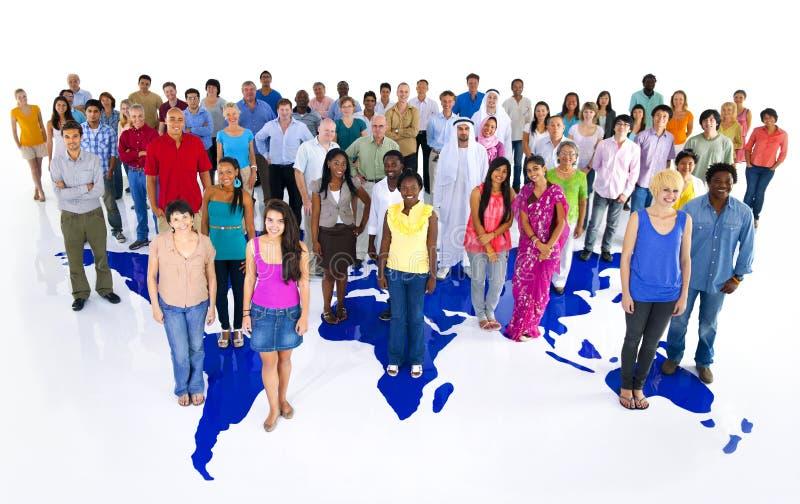 Μεγάλη ομάδα παγκόσμιων ανθρώπων με τον παγκόσμιο χάρτη στοκ φωτογραφίες