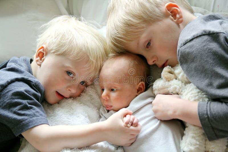Μεγάλοι Αδερφοί που αγκαλιάζουν τη νεογέννητη αδελφή μωρών στοκ εικόνες