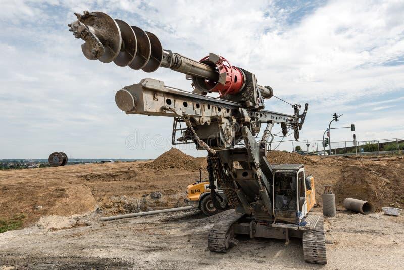 Μεγάλοι περιστροφικοί τρυπάνι και εκσκαφέας στο εργοτάξιο οικοδομής στοκ εικόνες