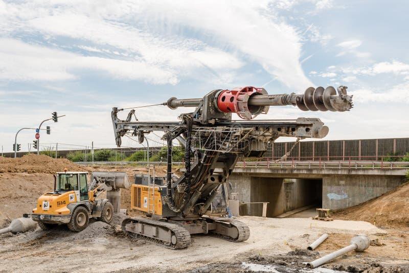 Μεγάλοι περιστροφικοί τρυπάνι και εκσκαφέας στο εργοτάξιο οικοδομής στοκ εικόνα