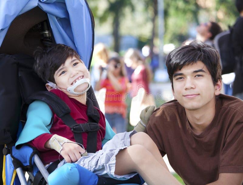 Μεγάλος Αδερφός που φροντίζει το με ειδικές ανάγκες αδελφό στην αναπηρική καρέκλα στοκ εικόνες