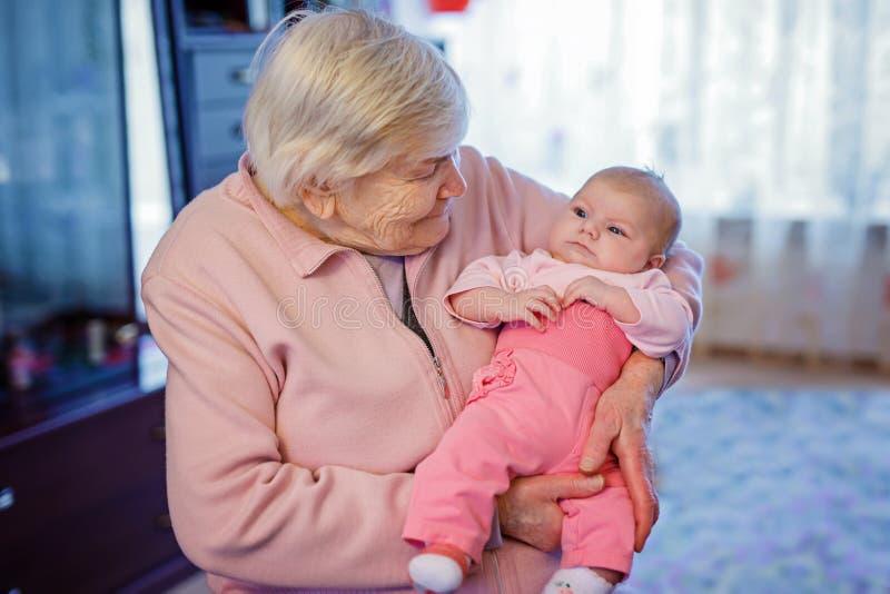 Μεγάλος - γιαγιά που κρατά το νεογέννητο εγγόνι μωρών στο βραχίονα στοκ εικόνες
