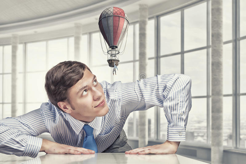 Μεγάλος επιχειρηματίας που τιτιβίζει από κάτω από τον πίνακα στοκ φωτογραφίες