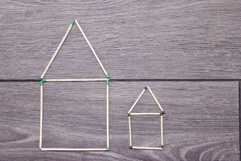 Μεγάλο και μικρό σπίτι φιαγμένο από αντιστοιχίες στο πάτωμα στοκ φωτογραφία