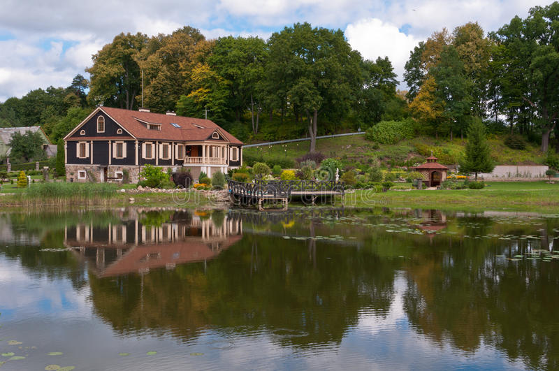 Μεγάλο οικογενειακό σπίτι μπροστά από τη λίμνη στο δάσος στοκ εικόνες
