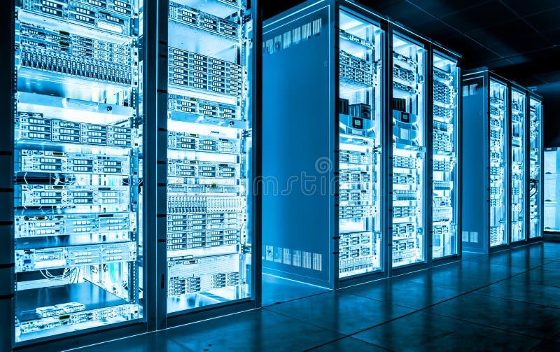 Μεγάλο δωμάτιο κεντρικών υπολογιστών στοιχείων σκοτεινό με το φωτεινό εξοπλισμό στοκ εικόνα