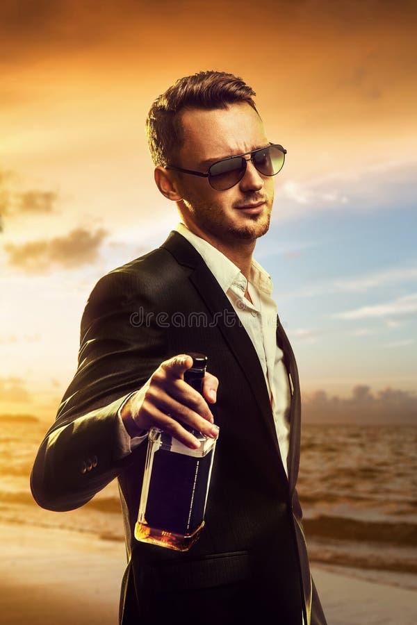 Μεθυσμένος νεαρός άνδρας με το ουίσκυ στοκ εικόνες