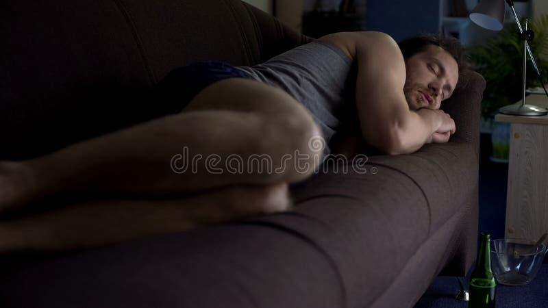 Μεθυσμένος ύπνος ατόμων στον καναπέ στο εσώρουχο, αποτυχημένος γάμος, που πίνει στο σπίτι στοκ φωτογραφία