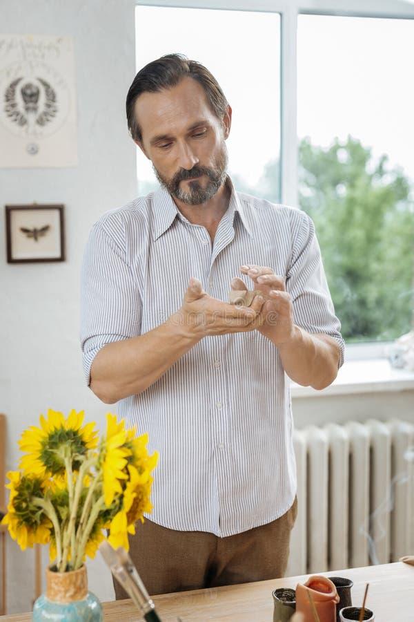 Μελαχροινός μαλλιαρός αγγειοπλάστης που κάνει μερικές δημιουργικές διακοσμήσεις στοκ εικόνα με δικαίωμα ελεύθερης χρήσης