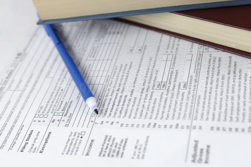 Μεμονωμένες έντυπο φορολογικής δήλωσης φόρου εισοδήματος και εκθέσεις βιβλίων σχετικά με το γραφείο εργασίας γραφείων στοκ φωτογραφίες