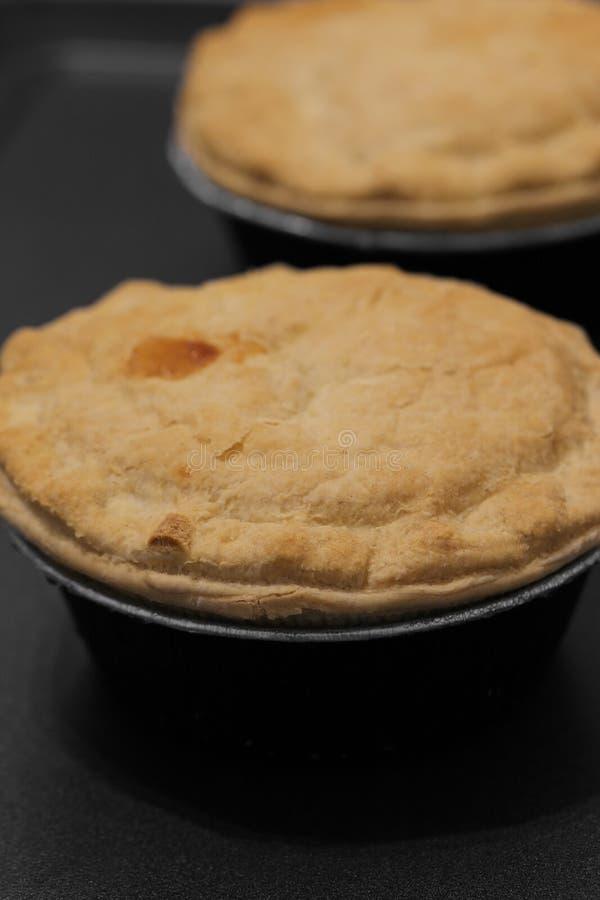 Μεμονωμένες πίτες μπριζόλας στο φύλλο αλουμινίου με ένα κάλυμμα ζύμης στοκ φωτογραφία με δικαίωμα ελεύθερης χρήσης