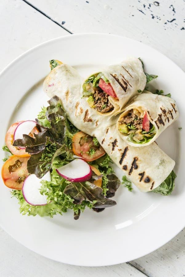 Μεξικάνικος ρόλος περικαλυμμάτων burrito βόειου κρέατος και σαλάτας στοκ εικόνα με δικαίωμα ελεύθερης χρήσης