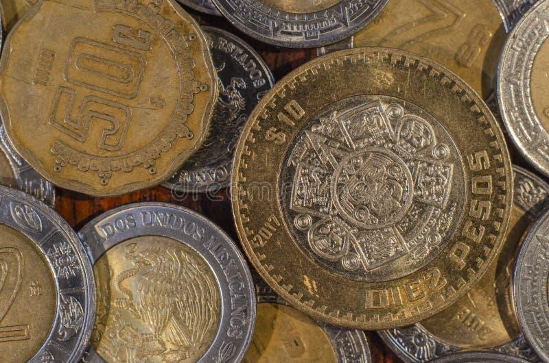 Μεξικάνικο νόμισμα στη μέση άλλων νομισμάτων σε έναν πίνακα του ξύλου στοκ φωτογραφία