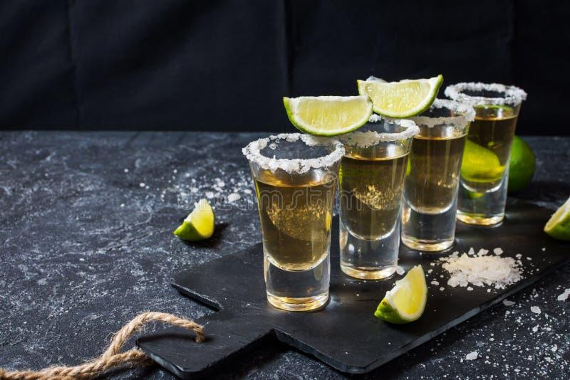 Μεξικάνικο χρυσό tequila με τον ασβέστη και άλας στο μαύρο υπόβαθρο πετρών στοκ εικόνες