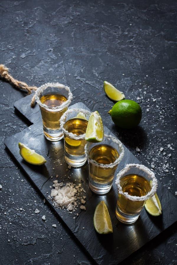 Μεξικάνικο χρυσό tequila με τον ασβέστη και άλας στο μαύρο υπόβαθρο πετρών στοκ φωτογραφία