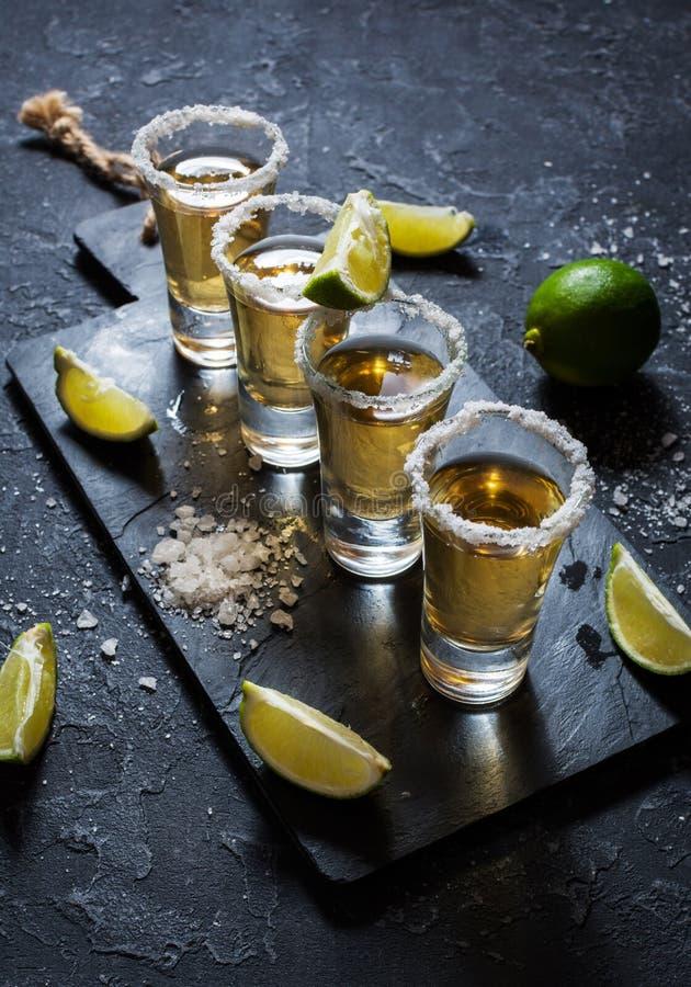 Μεξικάνικο χρυσό tequila με τον ασβέστη και άλας στο μαύρο υπόβαθρο πετρών στοκ εικόνα