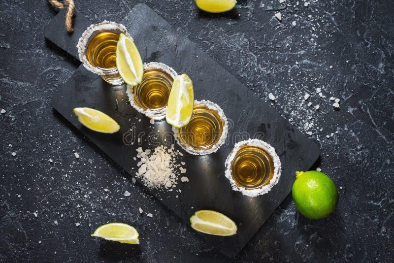 Μεξικάνικο χρυσό tequila με τον ασβέστη και άλας στο μαύρο υπόβαθρο πετρών στοκ εικόνες με δικαίωμα ελεύθερης χρήσης