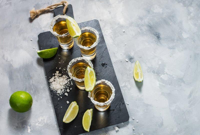 Μεξικάνικο χρυσό tequila με τον ασβέστη και άλας στο μαύρο υπόβαθρο πετρών Τοπ όψη στοκ εικόνες με δικαίωμα ελεύθερης χρήσης