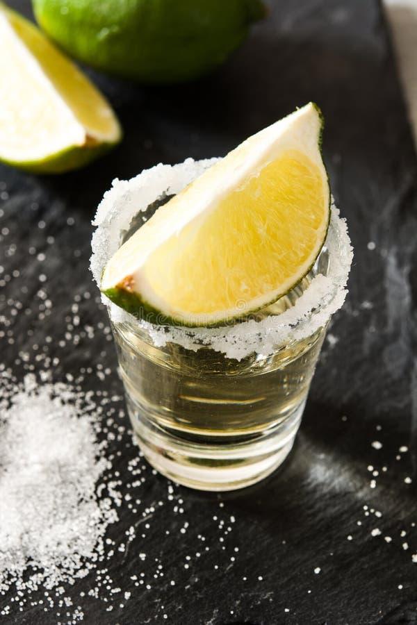 Μεξικάνικο χρυσό Tequila με τον ασβέστη και άλας στο μαύρο υπόβαθρο στοκ φωτογραφία με δικαίωμα ελεύθερης χρήσης