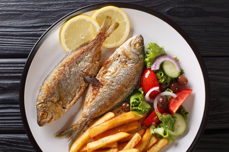 Μερίδα των τηγανισμένων ψαριών φάγρων Salema με το λεμόνι, τις τηγανιτές πατάτες και την κινηματογράφηση σε πρώτο πλάνο σαλάτας φ στοκ εικόνες