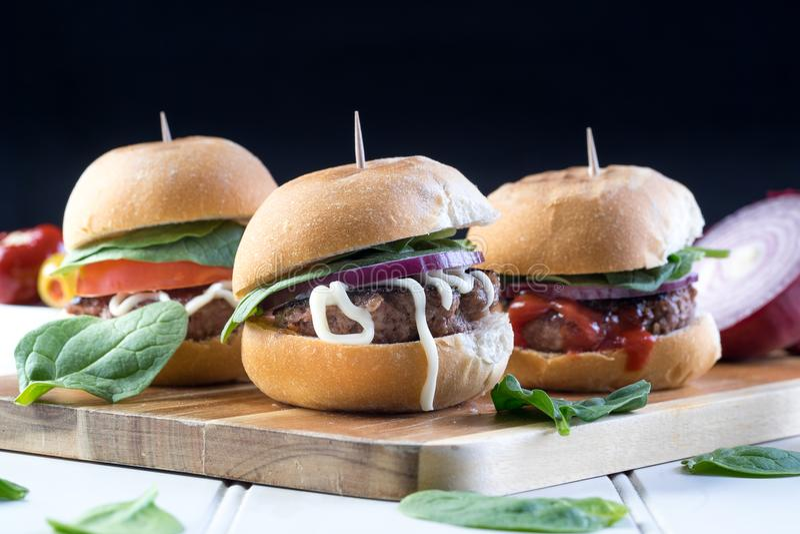 Μερίδιο ολισθαινόντων ρυθμιστών burgers βόειου κρέατος κόμματος στοκ εικόνες