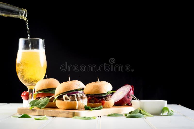 Μερίδιο ολισθαινόντων ρυθμιστών burgers βόειου κρέατος κόμματος στοκ εικόνες με δικαίωμα ελεύθερης χρήσης