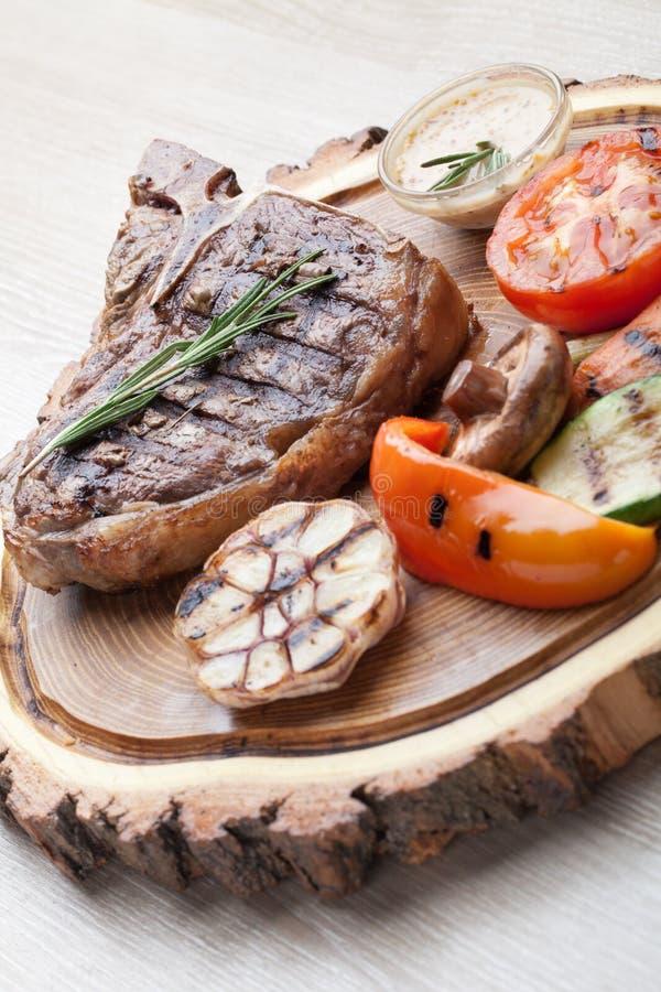 Μερίδα BBQ t-bone της μπριζόλας με τη σάλτσα και τα ψημένα στη σχάρα λαχανικά στοκ εικόνες
